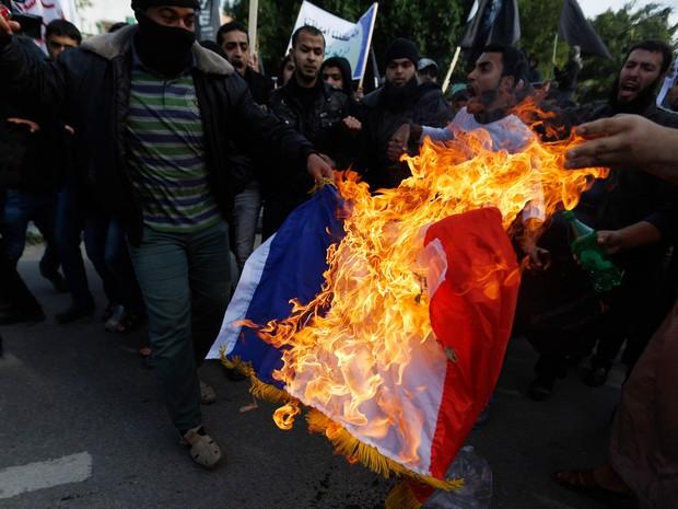 Um salafista palestino queima uma bandeira da França durante um protesto contra a impressão de desenhos satíricos do profeta Maomé pelo jornal Charlie Hebdo durante passeata para o Centro Cultural Francês na cidade de Gaza (Foto: Mohammed Abed/AFP)