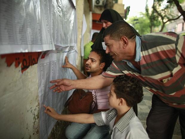 Eleitores buscam seus nomes em um colégio eleitoral de Cairo neste domingo (17). Votação irá determinar primeiro presidente eleito democraticamente no país. (Foto: REUTERS/Suhaib Salem)