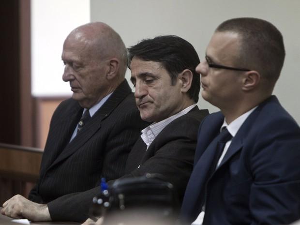 Médico Lutfi Dervishi é cercado por seus advogados de defesa em uma sala do tribunal, em Pristina, Kosovo, nesta segunda-feira (29) (Foto: AP Photo / Visar Kryeziu)