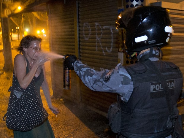 Policial joga spray de pimenta em manifestante no Rio de Janeiro (Foto: Victor R. Caivano/AP)