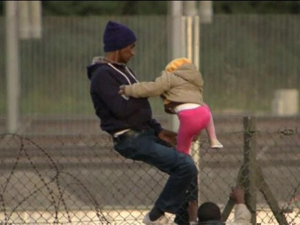 Imagens mostram momento em que migrante ajuda uma criança a atravessar cerca na região do Canal da Mancha (Foto: Reprodução/BBC)