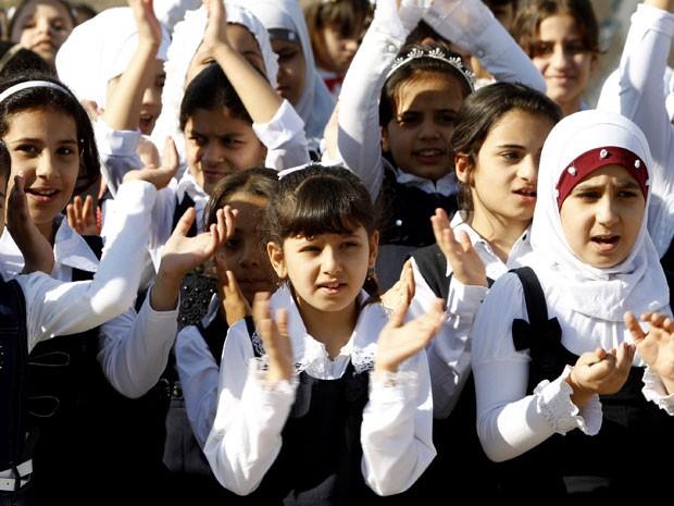 Meninas rezam antes de entrar para a escola em Bagdá (Foto: Ahmed Saad/Reuters)