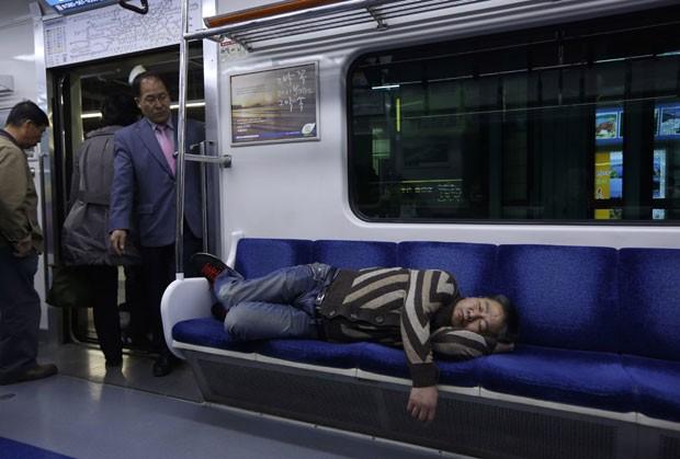 Um passageiro foi fotografado tirando uma soneca em um trem nesta sexta-feira no metrô de Seul, na Coreia do Sul (Foto: Kin Cheung/AP)