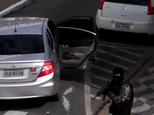 Enquanto comparsas estavam dentro do banco, assaltante vigiava praça (Foto: Reprodução/ TV TEM)