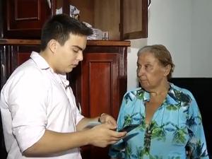 Universitário explica para aposentada como funciona o aplicativo Energia (Foto: Reprodução/TV Anhanguera)