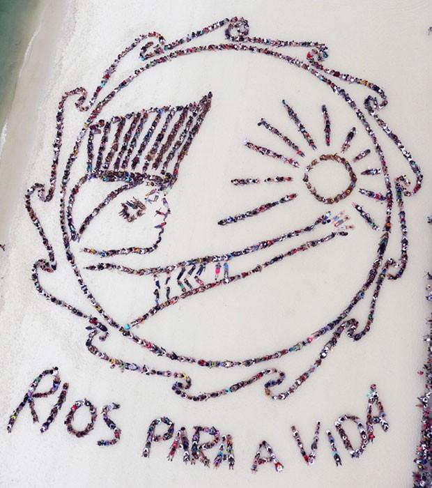 Desenho humano visto do alto traz a mensagem: 'Rios para a vida' (Foto: AFP)