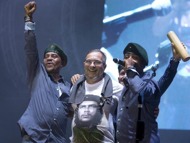 O líder máximo das Forças Revolucionárias da Colômbia, Rodrigo Londono (centro), também conhecido como Timochenko, abraça cantores do grupo Southern Rebels durante a 10ª conferência das Farc na Planície do Yari, sul da Colômbia, na noite de domingo (18) (Foto: Ricardo Mazalan/AP)