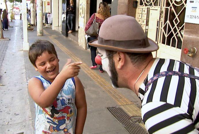 Guido brinca com criança na rua, vestido totalmente de palhaço (Foto: Reprodução / TV TEM)