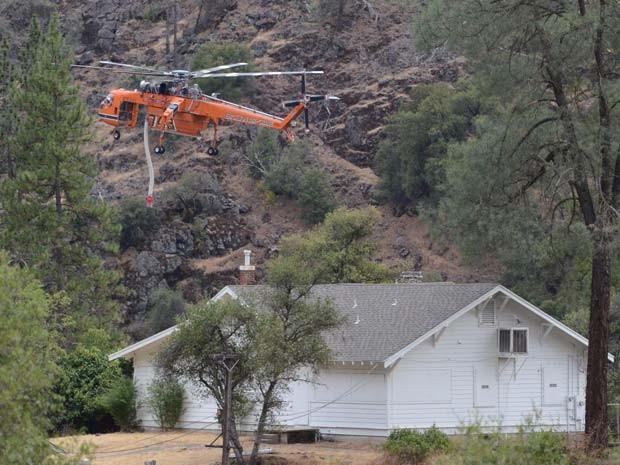 Helicóptero sobrevoa casa de El Portal nesta segunda-feira (28) antes de lançar água do Rio Merced (Foto: AP Photo/The Fresno Bee, Mark Crosse)