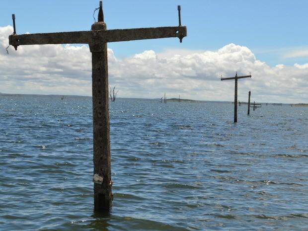 Postes de energia elétrica não foram retirados antes da inundação da cidade e ressurgiram (Foto: Gabriela Alves/G1)