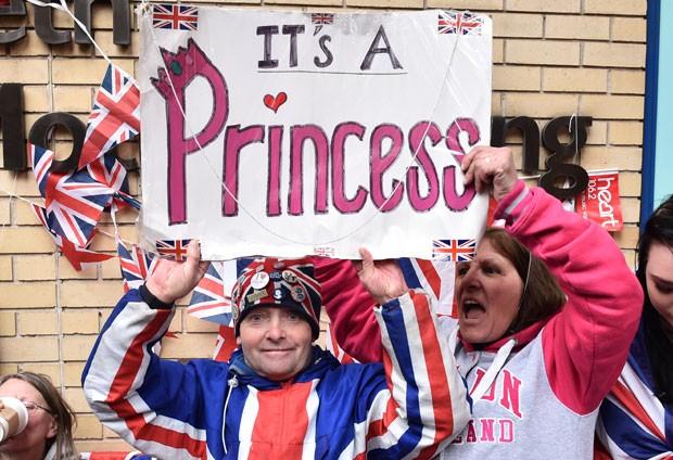 Fãs da família real comemoram o nascimento da nova princesa, filha de Kate Middleton e do príncipe William, em frente ao hospital onde ocorreu o nascimento em Londres (Foto: Leon Neal/AFP)