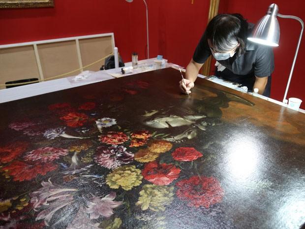 Restaurador trabalha em 'Flores', do mestre italiano do século 17 Paolo Porpora; tela já voltou à exibição em museu de Taiwan após ser danificado sem querer por garoto de 12 anos (Foto: Divulgação)