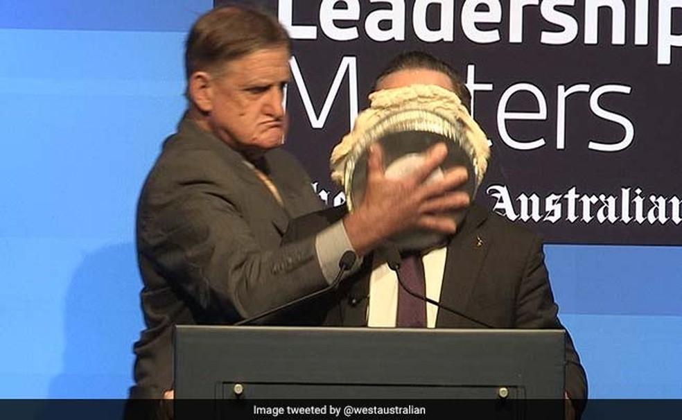 Homem joga torta na cara do presidente da Qantas, Alan Joyce, em evento na Austrália (Foto: Reprodução/Twitter/NDTV)
