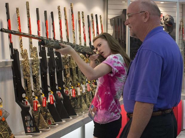 Rebecca Donnelly, de 14 anos, e o seu Brian Donnelly testam armas em evento da NRA em Houston, no Texas. (Foto: Reuters)