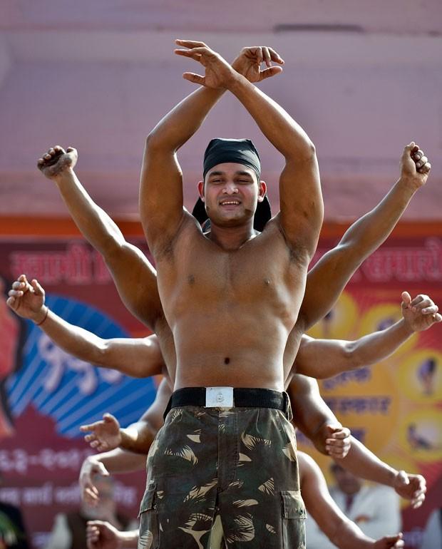 Um fisiculturista indiano parecia ter 12 braços ao ser fotografado durante um pratica matinal de ioga, nesta segunda-feira (18), em Nova Délhi, na Índia (Foto: Prakash Singh/AFP)