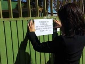 Juíza afixa cartaz de interdição no portão do abrigo em Águas Lindas de Goiás (Foto: Divulgação/ TJ-GO)