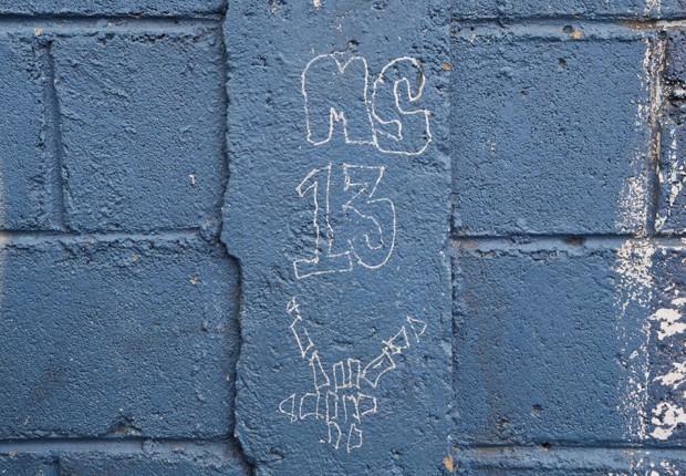 Grafite em muro da escola Jose Ramon Montoya faz referência à gangue Mara Salvatrucha (ou MS-13) (Foto: Esteban Felix/AP)
