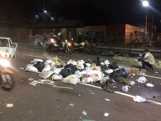 População chegou a tentar atear fogo em lixo jogado na rua em frente à sede do Sinetram (Foto: Rickardo Marques/G1 AM)