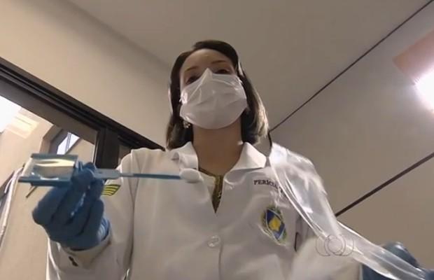 Amostra genética dos presos é coletada com haste de plástico em Goiânia, Goiás (Foto: Reprodução/TV Anhanguera)
