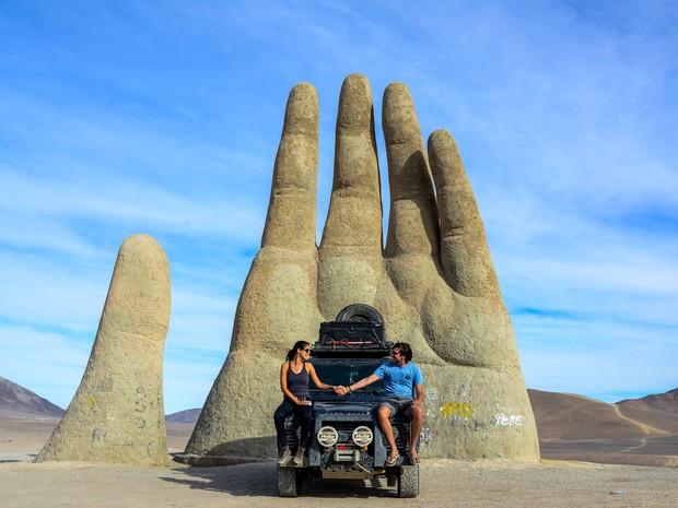 Rafael Ávila e sua esposa Isabela Miranda ao lado da 'Mão do deserto', nome da obra criada pelo escultor Mário Irarrázabal. Composta por ferro e cimento, a escultura possui 11 metros de altura, localizada ao lado da estrada panamericana, no Chile (Foto: Rafael Ávila/VC no G1)
