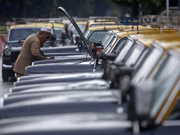 Taxista verifica motor de seu Padmini em Mumbai (Foto: Vivek Prakash/Reuters)