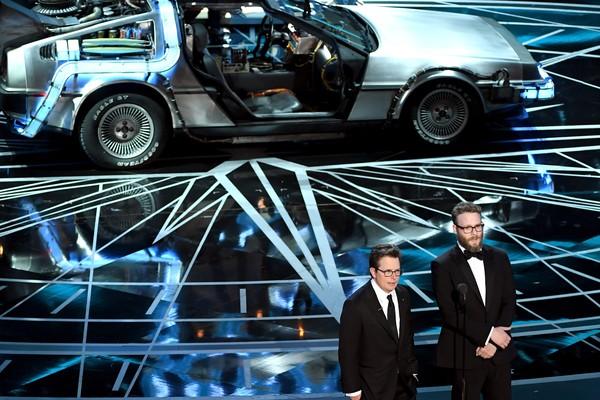 Michael J. Fox ao lado de Seth Roger durante a festa do Oscar que teve homenagem a De Volta para o Futuro (Foto: Getty Images)