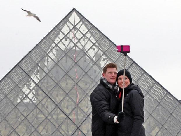 Casal tira foto com o 'pau de selfie' em frente ao museu do Louvre, em Paris (Foto: Remy de la Mauviniere/AP)