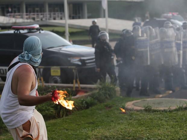 Manifestantes atira um coquetel molotov em direção a policiais durante protesto contra a PEC 55, que limita os gastos públicos para os próximos 20 anos, na Esplanada dos Ministérios, em Brasília (Foto: Eraldo Peres/AP)