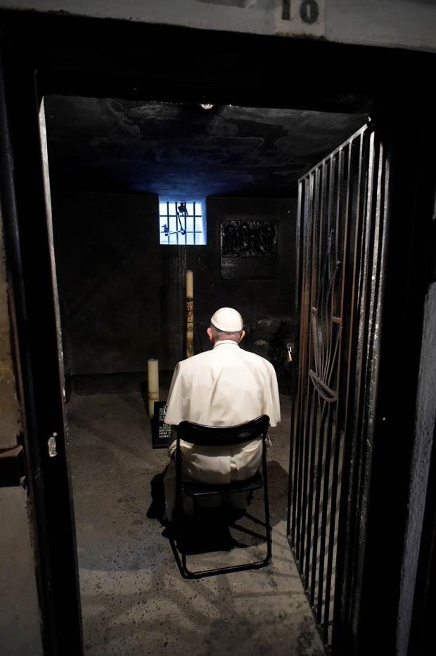 O Papa Francisco reza em uma cela do campo de extermínio nazista de Auschwitz, com a frase 'Arbeit Macht Frei' ('O trabalho liberta', em alemão), em Oswiecim, na Polônia, como parte da programação da Jornada Mundial da Juventude (Foto: Reuters/Osservatore Romano)