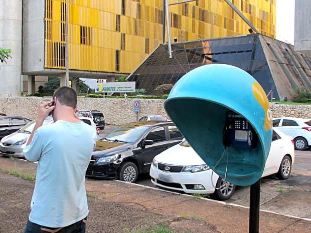 Homem fala ao celular ao lado de orelhão, em Brasília (Foto: Lucas Nanini/G1)