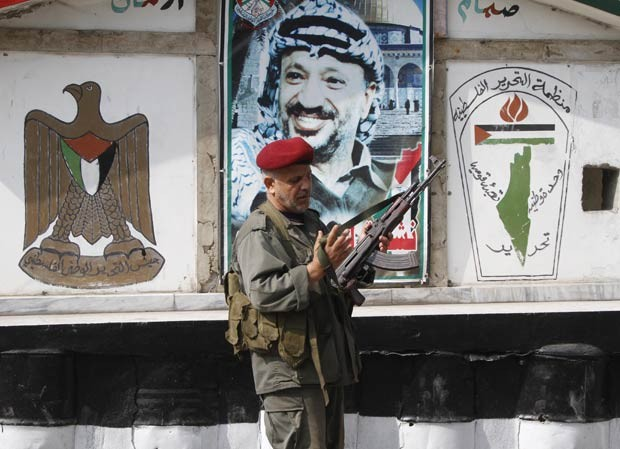Membro do braço armado da OLP monta guarda no campo de refugiados palestinos de Ein el-Hilweh, in Sidon, no Líbano, em 19 de junho de 2012, com pintura de Yasser Arafat ao fundo (Foto: AP)