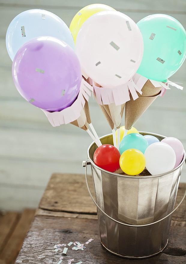 Bexigas não se limitam a decorar festas infantis. Como são fáceis de usar e fazem a maior vista, dá para abusar e encher a casa. A dica aqui é transformá-las em sorvetinhos: cones de papel kraft servem de casquinha para as bolas coloridas.   (Foto: Rogério Voltan/Casa e Comida)