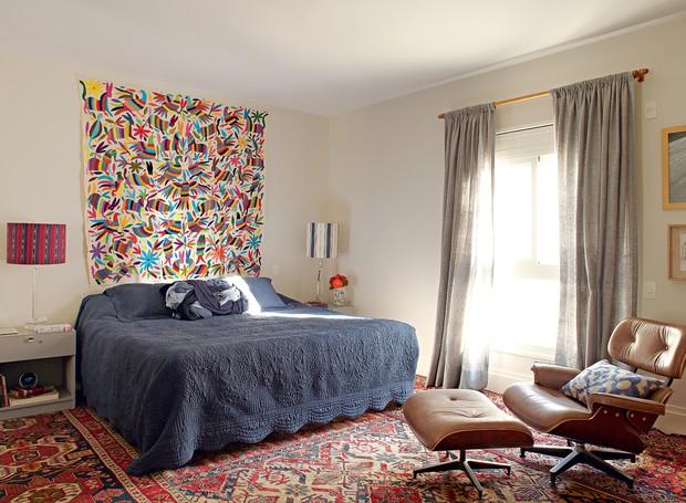 O piso do quarto de casal é forrado por Kilim e passadeiras, estas da By Kamy. Enxoval, da Trousseau. A colcha bordada, trazida do México, faz o papel de cabeceira. Cortina de seda, da Aladim Decorações, feita pela Tapeçaria Strauss (Foto: Victor Affaro)