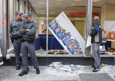 Policiais fazem segurança do lado de fora de uma agência bancária que foi praticamente toda depredada na noite desta terça-feira (18) (Foto: Eliária Andrade / Agência O Globo)