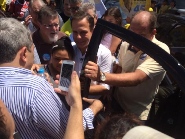 Doria tira foto com eleitores durante caminhada em feira (Foto: Andressa Roge/G1)