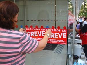 Funcionária coloca cartaz de greve em agência na Avenida Paulista (Foto: Fábio Tito/G1)