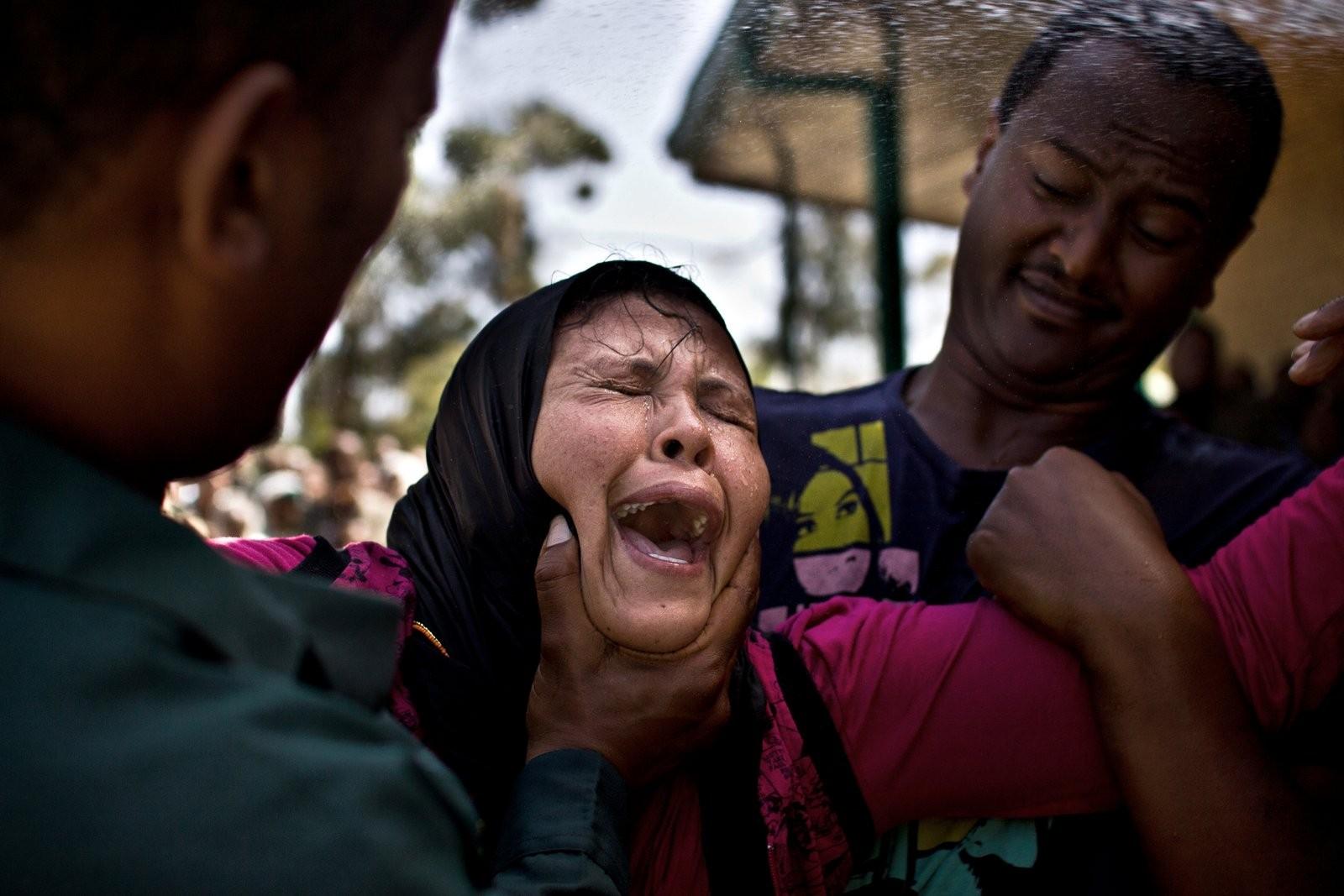 Žena v davu pláče poté, co se jí kněz Memihir Girma Wendimu snaží vyhnat démony z těla u kostela Yerer Sellassie na okraji Addis Abeby v Etiopii v lednu 2014.Oběti černé magie nebo různých druhů démonů k němu chodí a bezpodmínečně věří v jeho svatou pomo (Foto: David Tesinsky)