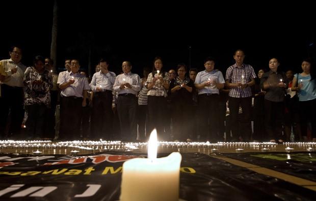 Famílias fazem orações durante vigília em praça de Kuala Lumpur (Foto: Manan Vatsyayana/AFP)