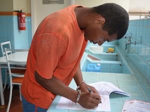 Algemado, pai assina documento de prisão em Piracicaba (Foto: Fernanda Zanetti/ G1)