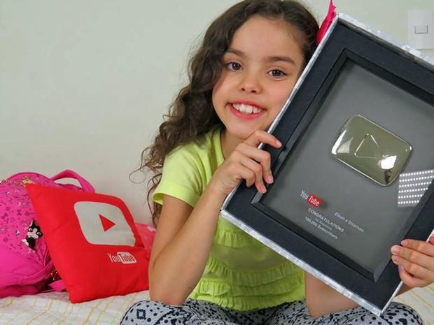 Eloah Lourenço, de 9 anos, segura a placa de 100 mil inscritos no canal do Youtube (Foto: Elaine Lourenço/Arquivo Pessoal)