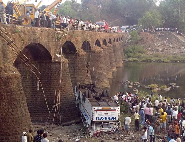 Resgatistas e passantes observam destroços de ônibus que caiu de ponte no distrito de Ratnagiri, no estado indiano de Maharashtra, nesta terça-feira (19) (Foto: Reuters)
