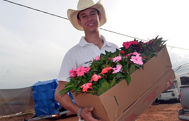 Jean Korsten Ferreira mostra flores plantadas em sua propriedade (Foto: Luciano Calafiori/G1)