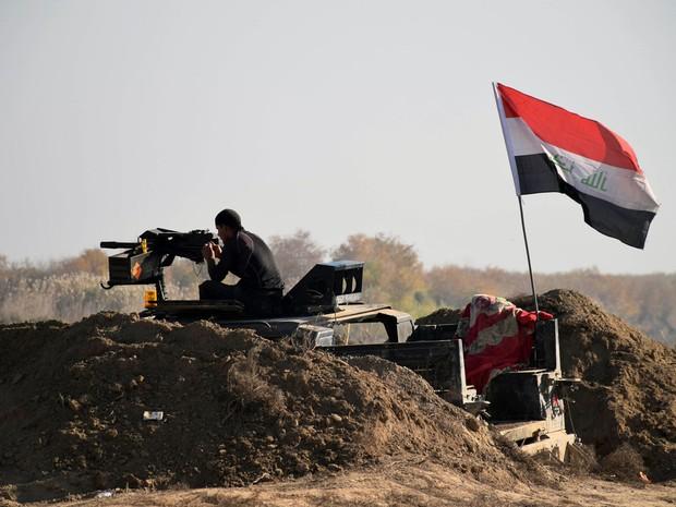 Forças iraquianas hasteiam bandeira próximo do centro de Ramadi. Exército anunciou nesta segunda-feira (28) que a cidade foi liberada do poder do Estado Islâmico (Foto: AP)