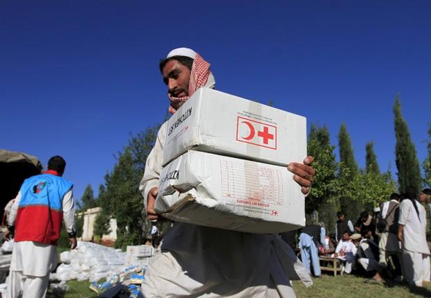 Afegão recebe ajuda da Cruz Vermelha em Behsud, no Afeganistão   (Foto: Parwiz/ Reuters)