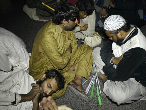 Manifestantes cegos sentam na rua durante manifestação por empregos em Lahore, no Paquistão (Foto: AFP Photo/Arif Ali)