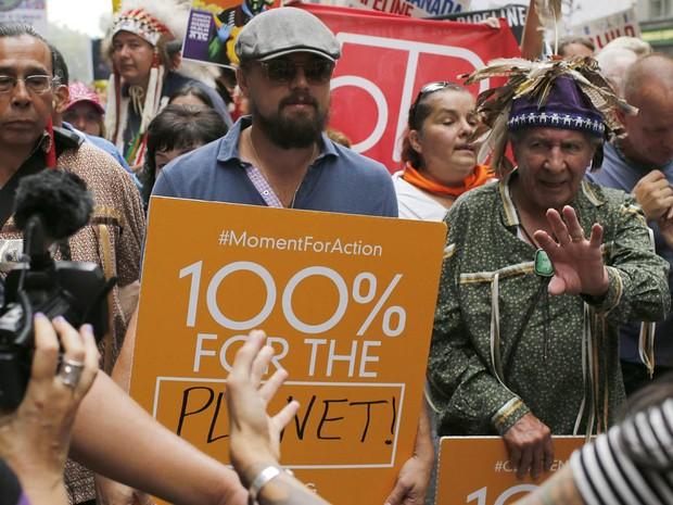O ator Leonardo DiCaprio marcha com manifestantes pró-sustentabilidade com uma placa de '100% para planeta' na Marcha Popular pelo Clima em Nova York (Foto: Eduardo Muñoz/Reuters)