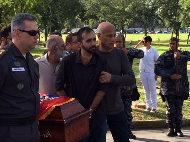 Marido de Drielle Lasnor amparado pelo tio da policial carregando caixão da esposa. No outro lado, Friederik Bassani, comandante do 14 BPM, onde ela trabalhava (Foto: Cristina Boeckel / G1)