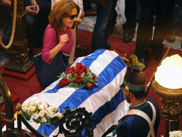 Helena Villagra, viúva do escritor uruguaio Eduardo Galeano, ao lado do caixão durante funeral em Montevidéu nesta terça (14) (Foto:  AFP PHOTO/MIGUEL ROJO)