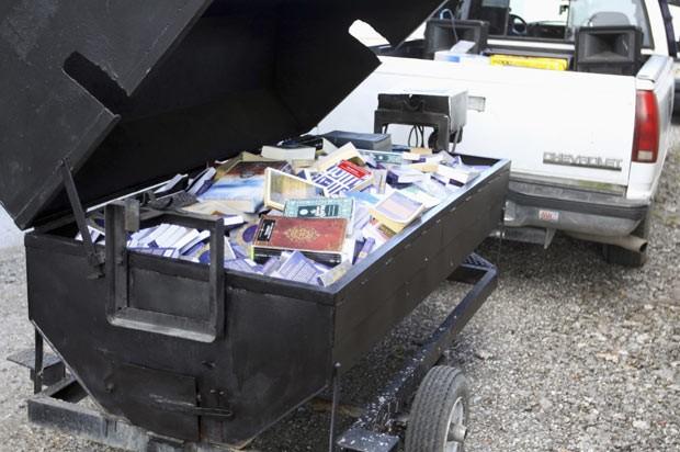 Foto divulgada pela polícia mostra a churrasqueira com exemplares do Corão embebidos de querosene (Foto: AFP)