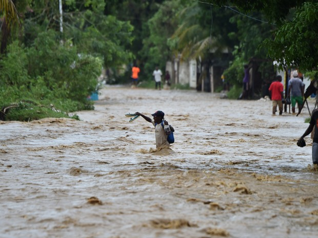 Haitianos tentam atravessar o rio La Rouyonne inundado nesta quarta-feira (5) na comunidade de Leogane, ao sul de Porto Príncipe (Foto: HECTOR RETAMAL / AFP)